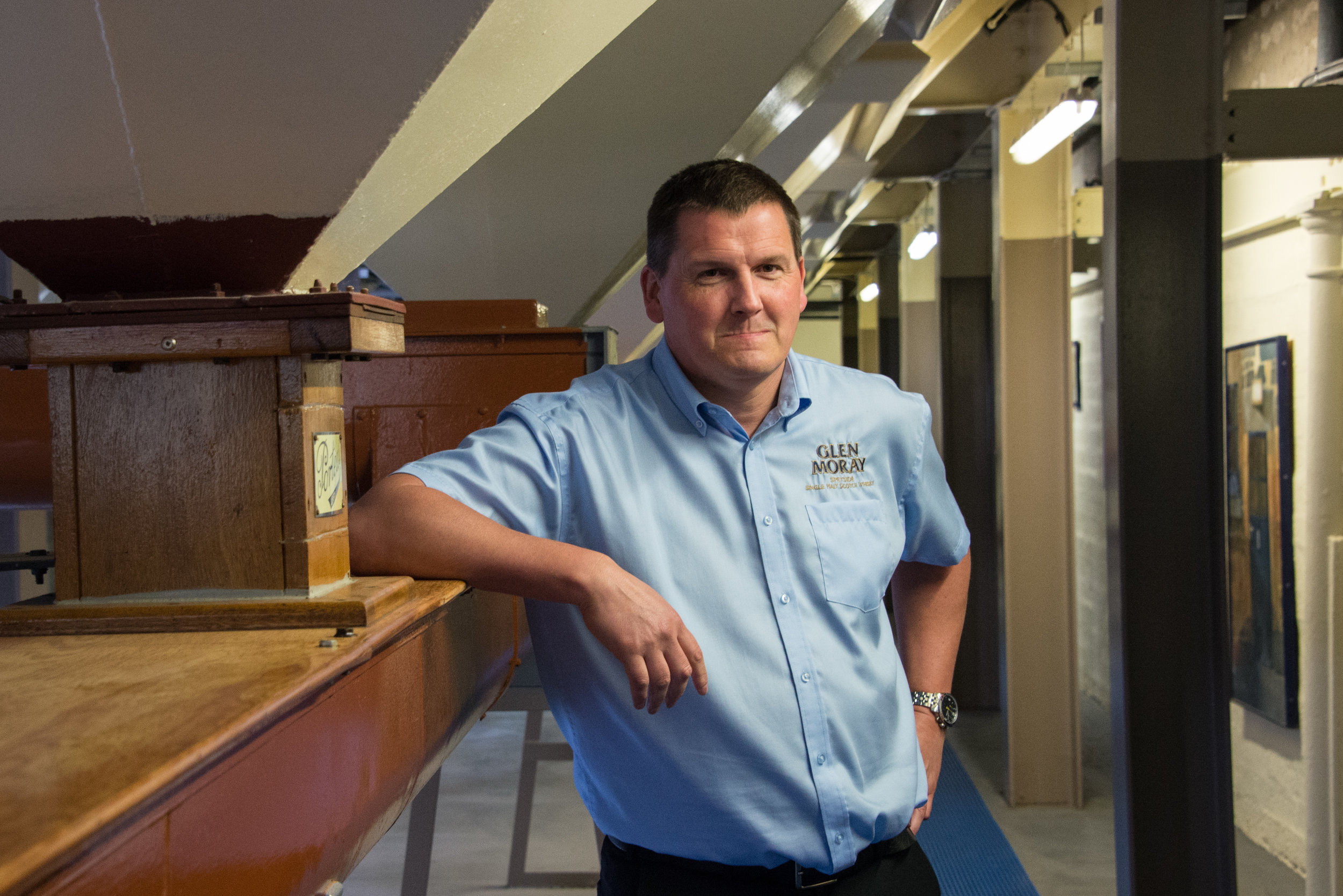 Glen Moray's Master Distiller Graham Coull stands in front of malt bins, which hold malted barley and date back to 1963.