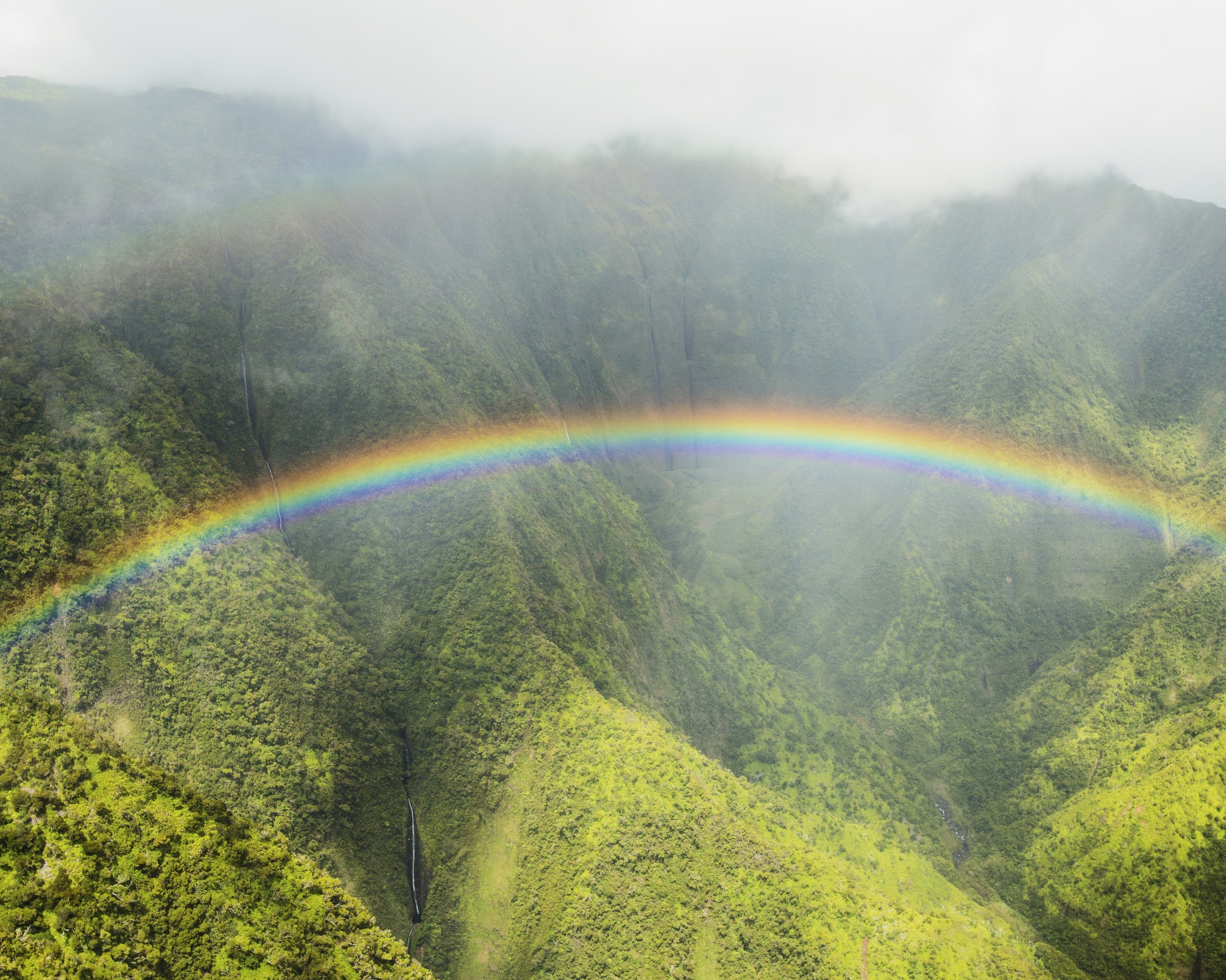 Waterfalls on the North Shore of Kauai with a perfect rainbow in front of them
