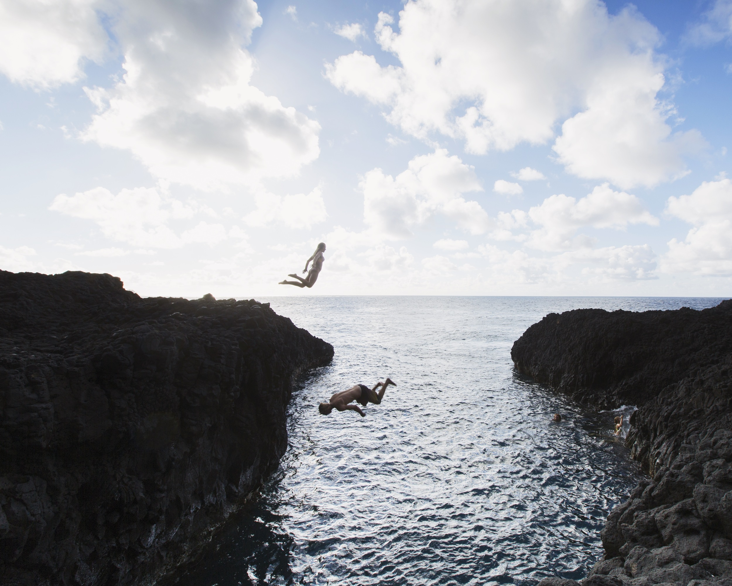 Two people jumping into the Pacific Ocean