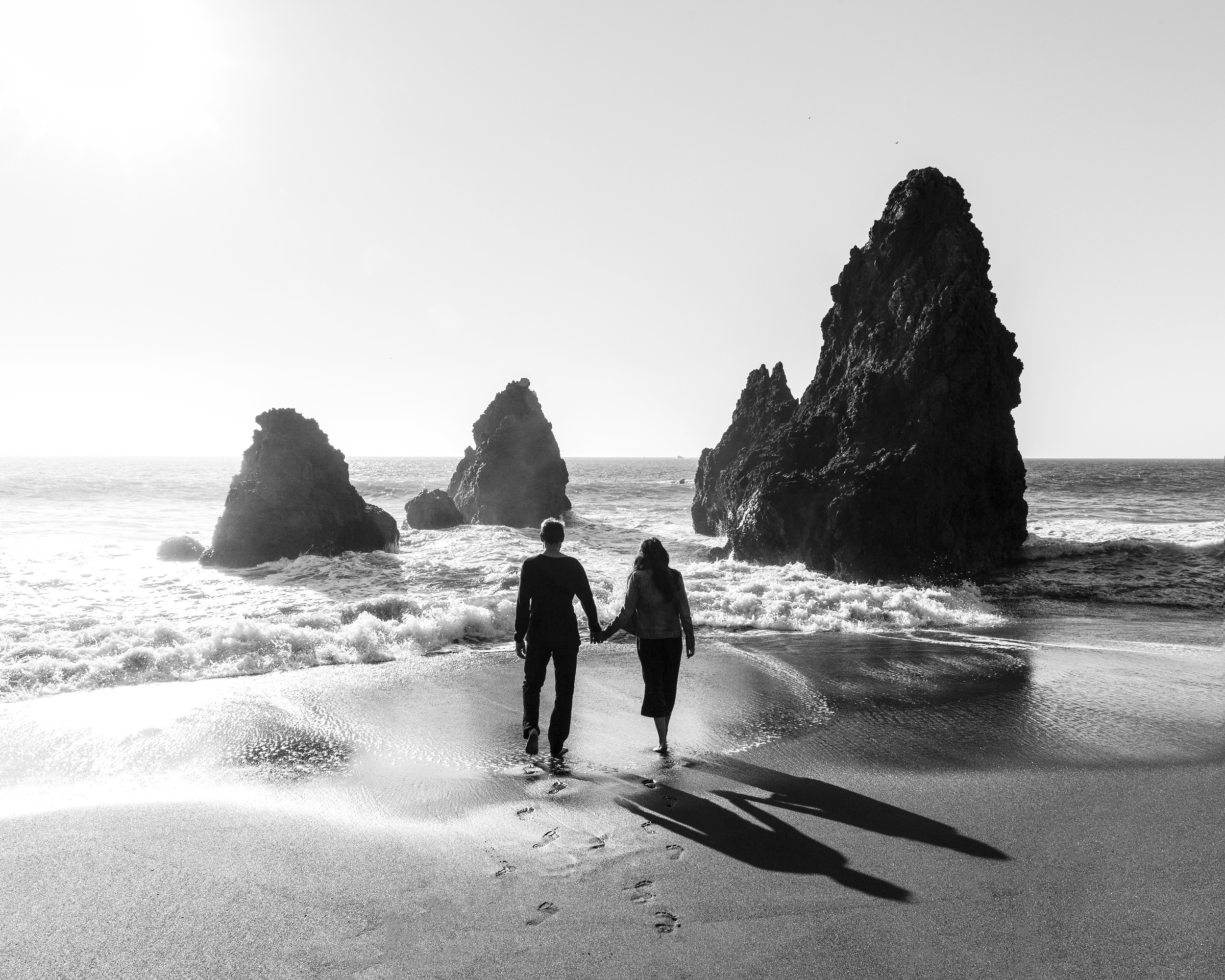 Best friends headed out to sea in between rocks at Rodeo Beach, California