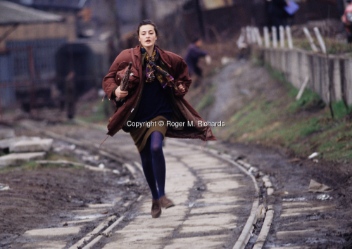 A young woman runs to avoid being shot by a Serb sniper during the siege of the city, Sarajevo, Bosnia and Herzegovina, April 1993.  Photography by Roger M. Richards