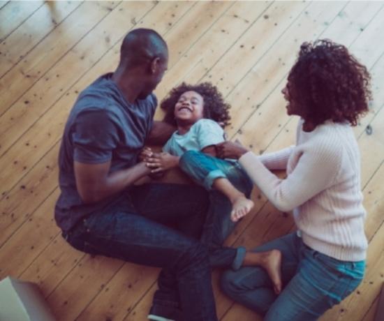 happy-parents-tickling-son-on-hardwood-floor-picture-id516014130.jpg