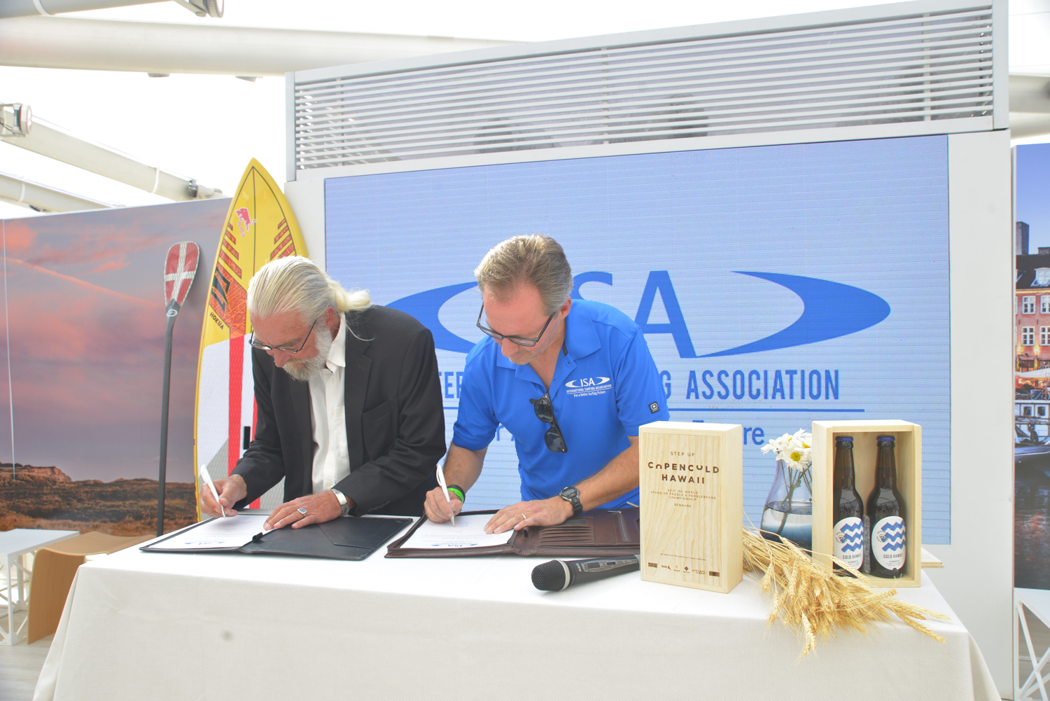 Finn Jorsal (left), president of Friends of Cold Hawaii, and Robert Fasulo (right), executive director, ISA, in the Danish National House in Rio, signing the COPENCOLD HAWAII – ISA World StandUp Paddle and Paddleboard Championship 2017 hosting agreement.