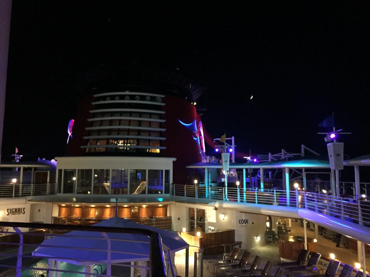The moon sets behind the Disney Magic.