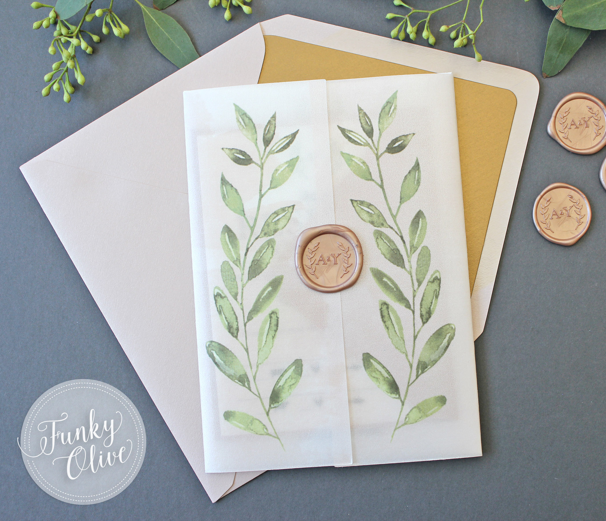 A soft watercolor wash of pale blush pairs with  gorgeous watercolor laurels, and a custom wax seal. Vellum wraps are one of the hottest, trendiest ways to package up your invitations.