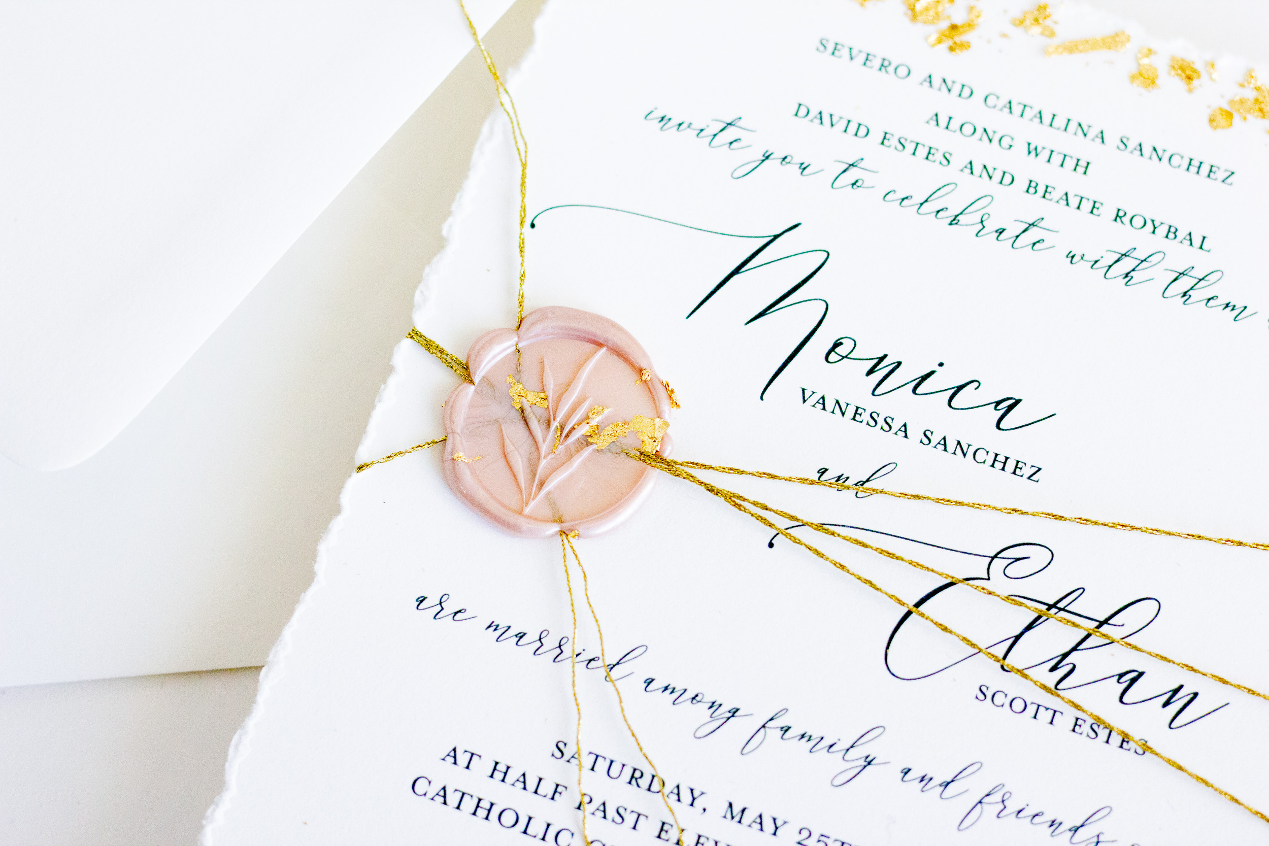 A deckled edge invitation, wrapped in the most beautiful gold twine, and sealed to perfection with a blush wax seal and a little gold flake because - we can!