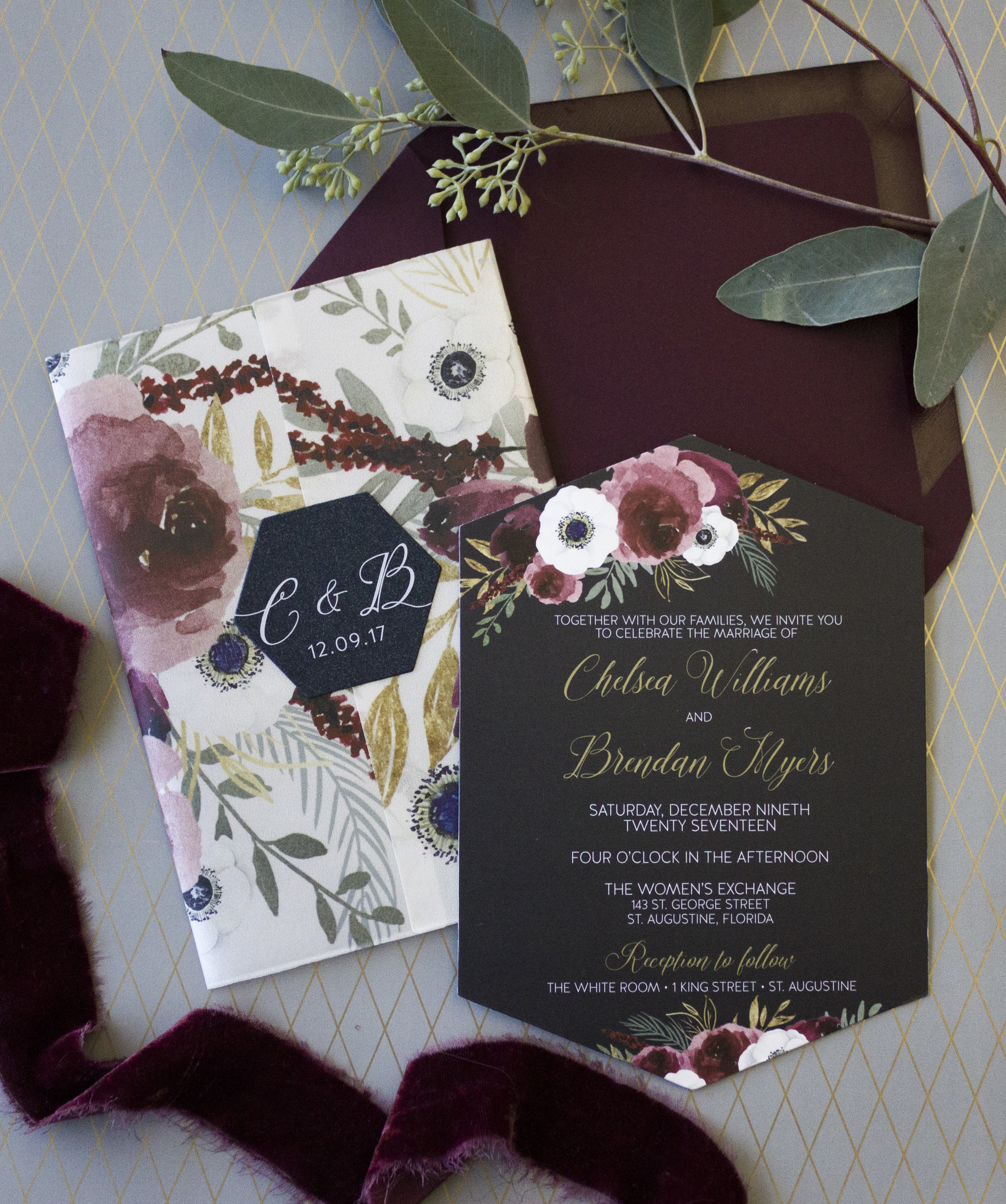This vellum wrapped invitation suite features a bold navy base, hexagon die cut pieces and a perfect burgundy envelope.