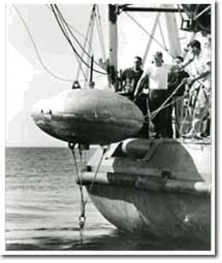 Figure 1:  Scientists lowering one of the six buoys used to make a circle, with the CUSS I drilling vessel positioning itself at the center using sonar. (Image via NSF)