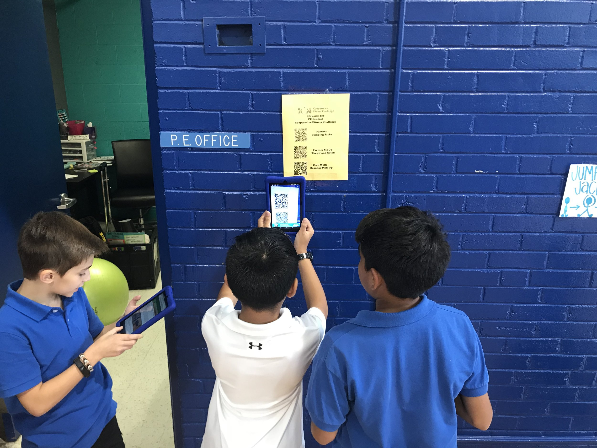 These students are using their kindles in the gym to find out what activity is next in their fitness challenge.