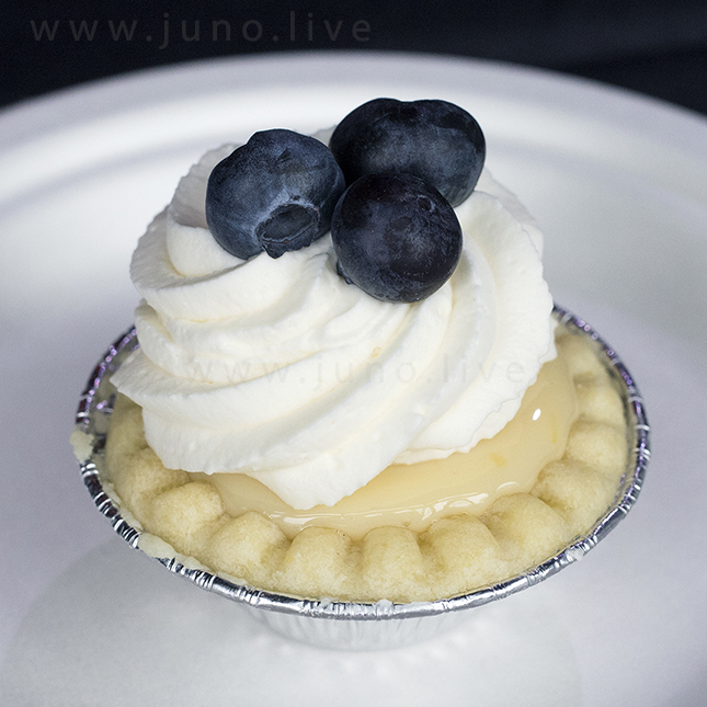 A miniature lemon pie dessert with whipped cream and fresh blueberries on a white paper plate placed on a dark tablecloth (December, 2018)