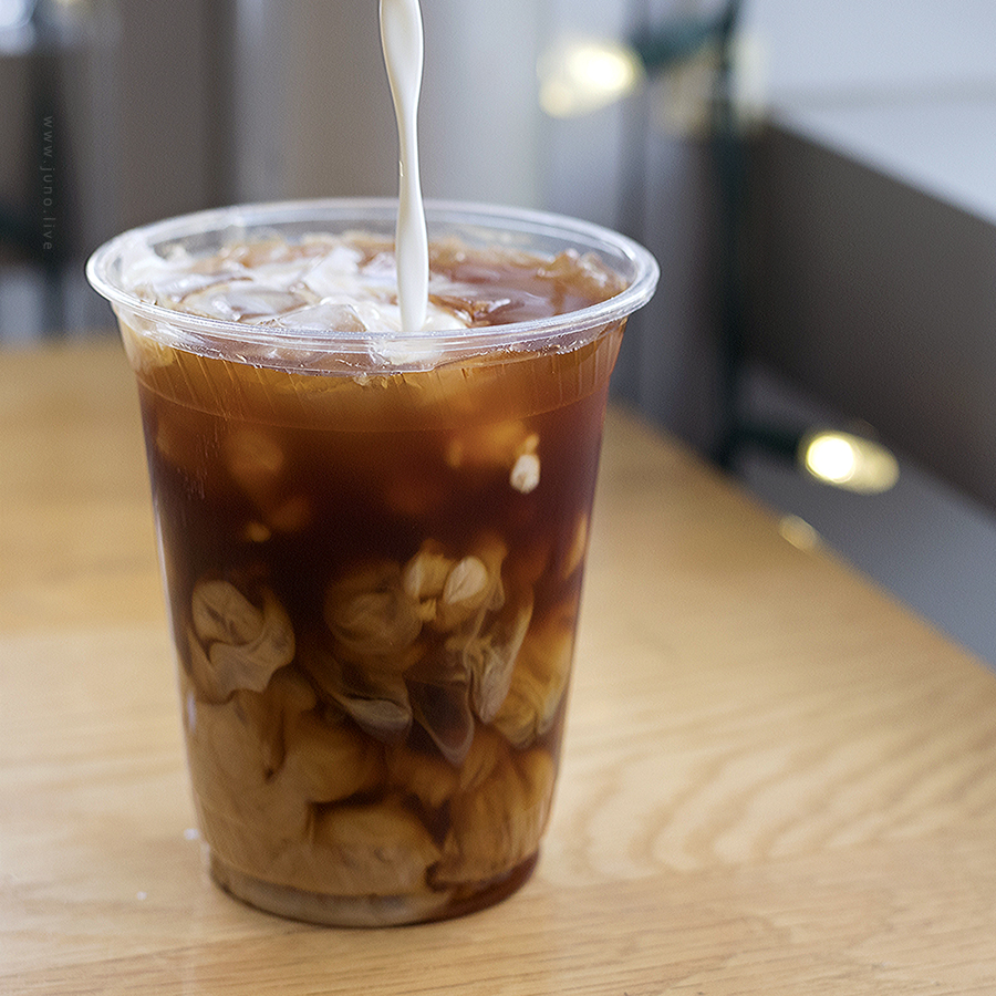 A photograph that captures the motion of milk pouring into an iced espresso drink known as an americano (December, 2018).