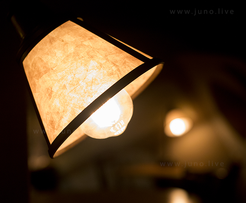 A bright lamp in a dim room of a coffee house.