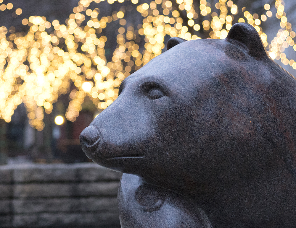 A bear sculpture against a background of lights in Jamison Square, a park located in the Pearl District of Portland, Oregon (December, 2018).