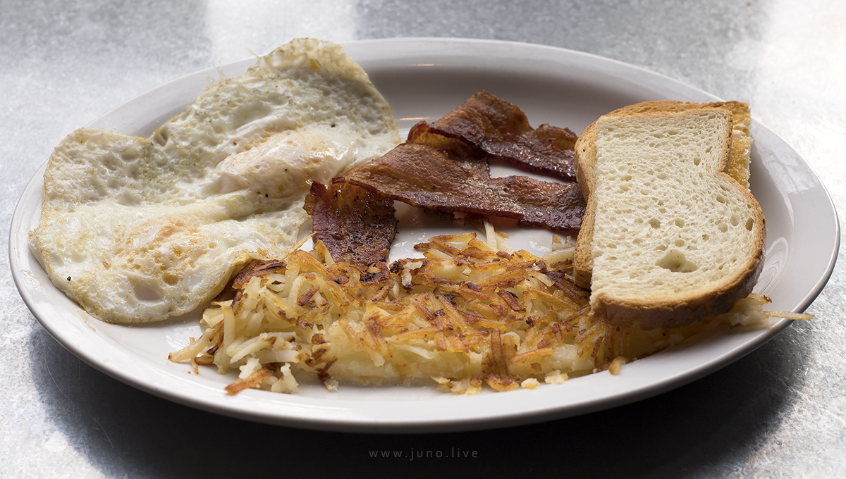 A breakfast meal including bacon, eggs, hash browns, and toast.