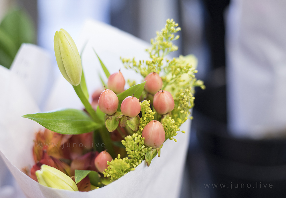 A bouquet of pink berries and green foliage wrapped in paper.