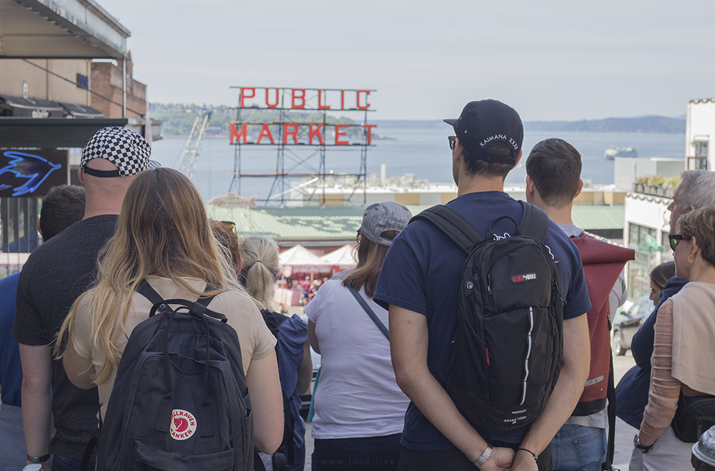 This is a photograph of tourists listening to a guide in front of Pike Place Market, a local farmers market in Seattle, Washington, United States.