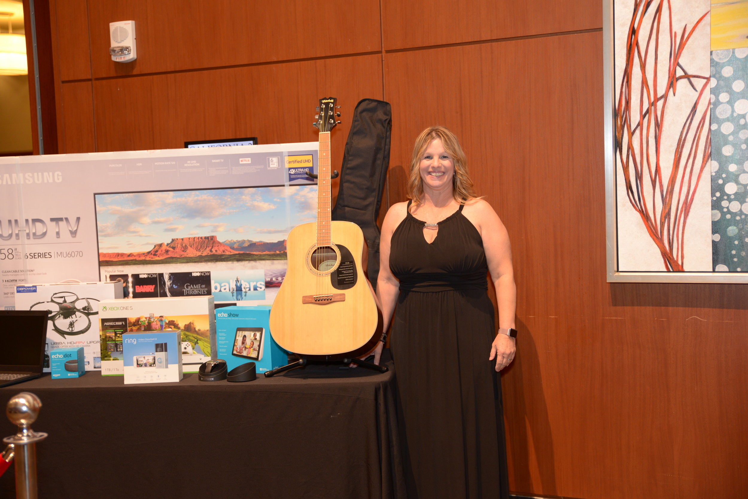 """Congratulations to Doris Martinez with AmeriFirst for winning the Opulent Opportunity Grand Prize! Doris went home with a Samsung - 58"""" Class Smart - 4K UHD TV with HDR, Mitchell D120PK Acoustic Guitar Value Package (Donated by Dottie Madison, Guitar Center), Lenovo 15.6"""" Laptop, Echo Dot (3rd Gen) - Smart speaker with Alexa, Xbox One S 1TB Minecraft Creator Bundle, Ring Video Doorbell 2, Echo Show (Donated by David Nelson, Nelson Engineers), DBPOWER Discovery Wifi FPV Camera Drone, Angels vs Dodgers (4 tickets + parking, Donated by Ray Allard, Allard Engineering), Citizen Men's Solar Wristwatch, & a One Week Stay at Private Condo Resort in Palm Desert (Donated Hunsaker & Associates)."""
