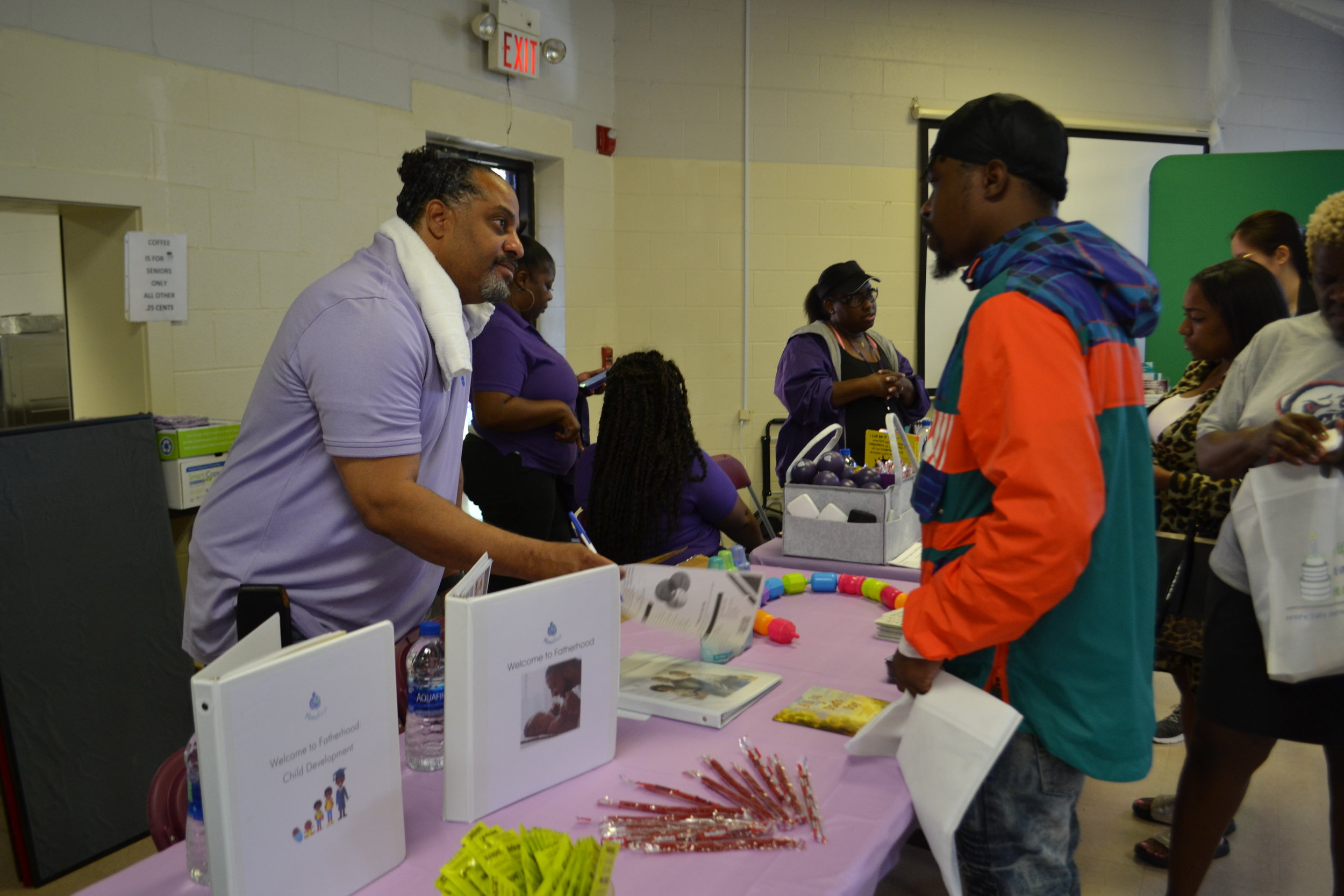 MomsFirst Fatherhood Coordinator, Ronald White, engaging with a father at the One Life, One Voice, One Community Baby Buggy Walk event for National Infant Mortality Awareness Month.