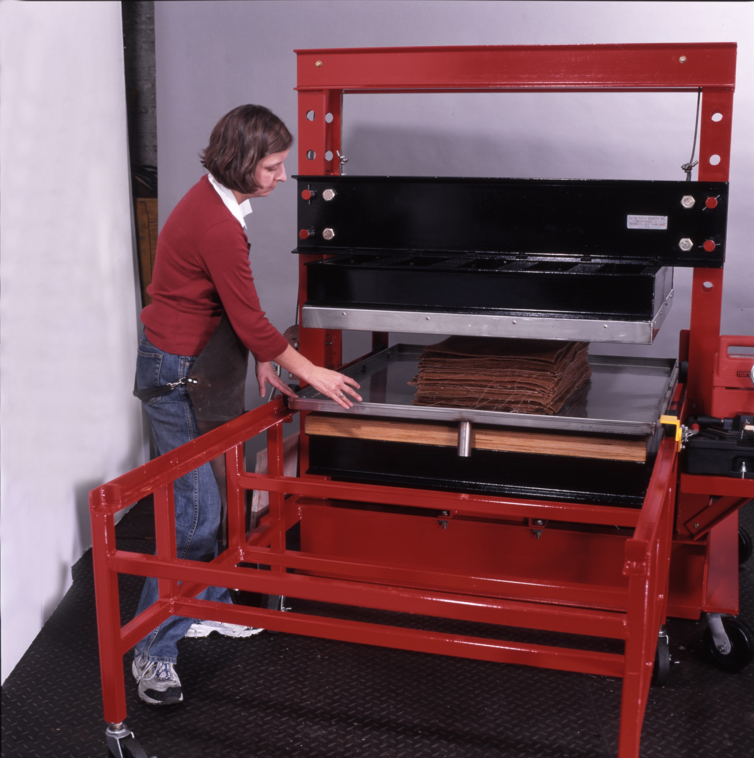 Pushing the stainless steel couching tray into the press