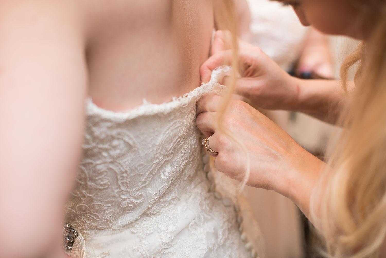 14 bridesmaids help zip up the bride's dress.jpg