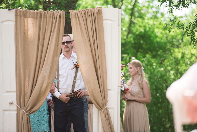 23 Groom peers through curtain as he waits to come down the aisle.jpg