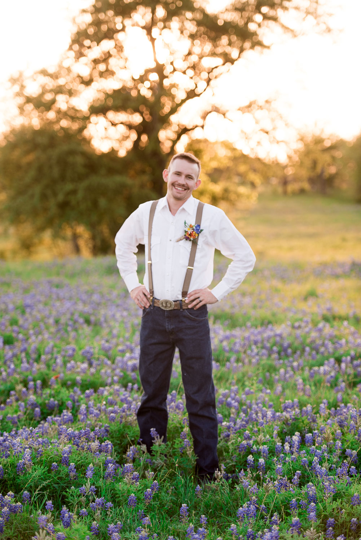 89 groom photos in field of bluebonnets with suspenders.jpg