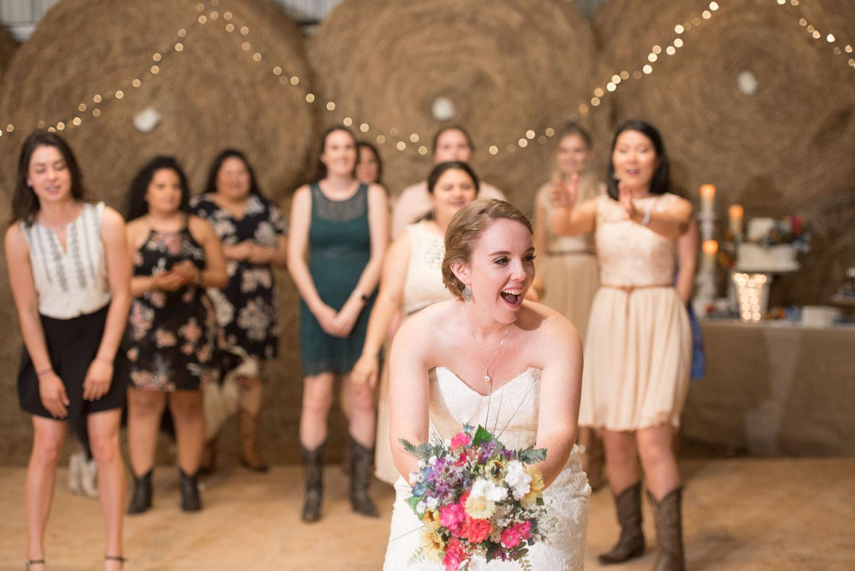 121 bride tosses bouquet to girls in barn wedding.jpg