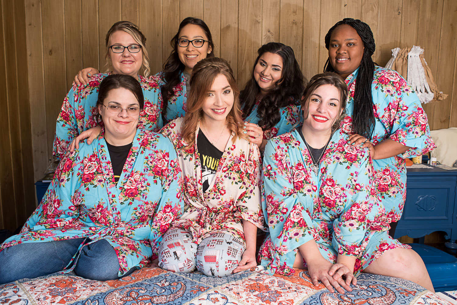 28 bridesmaids in matching robe on bed.jpg