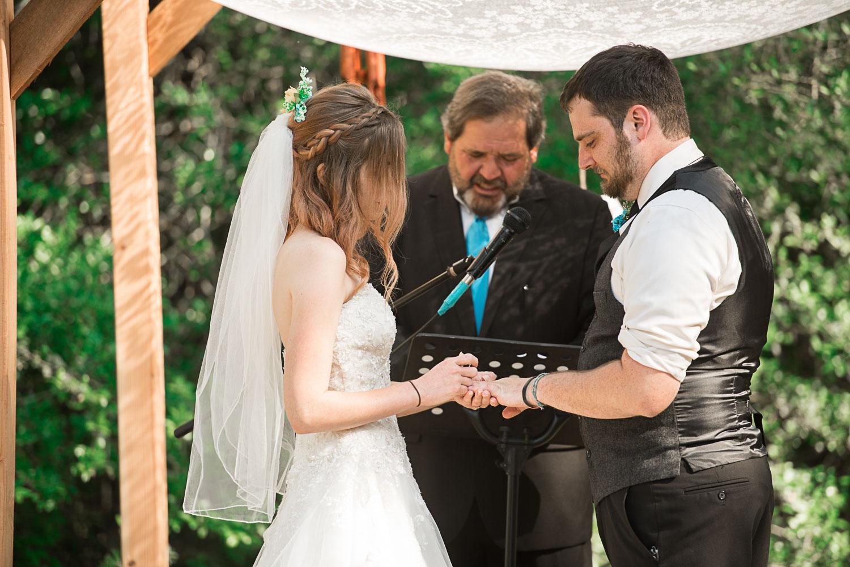 75 bride puts on grooms ring.jpg
