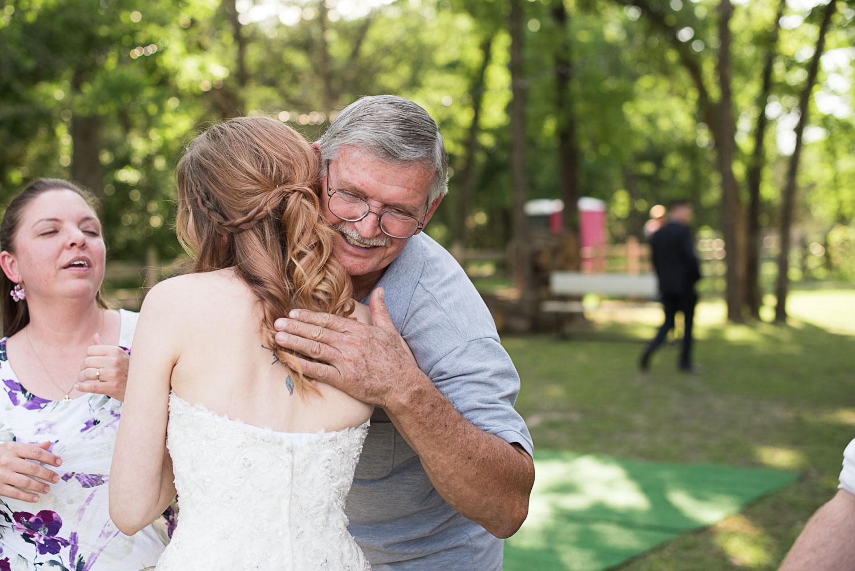 105 bride hugging wedding guests at family farm.jpg