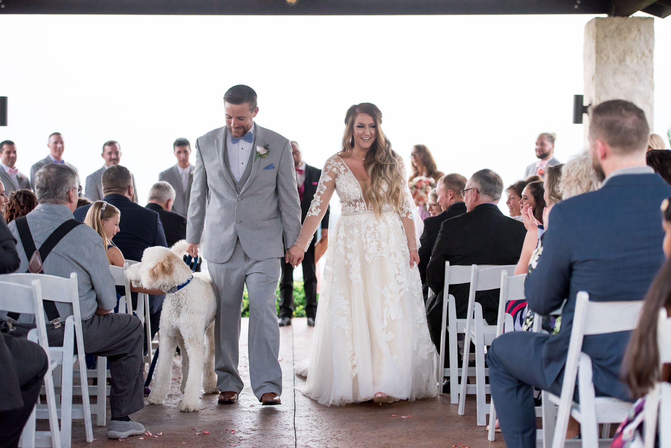 87 bride and groom walk down aisle with golden doodle.jpg