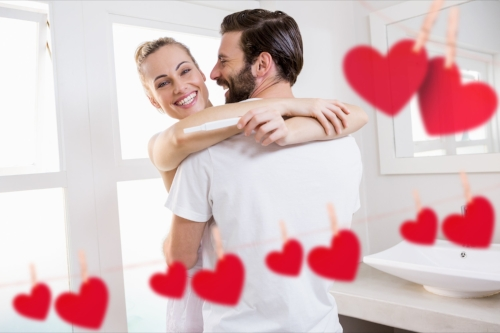 Red hanging heart and couple embracing each other