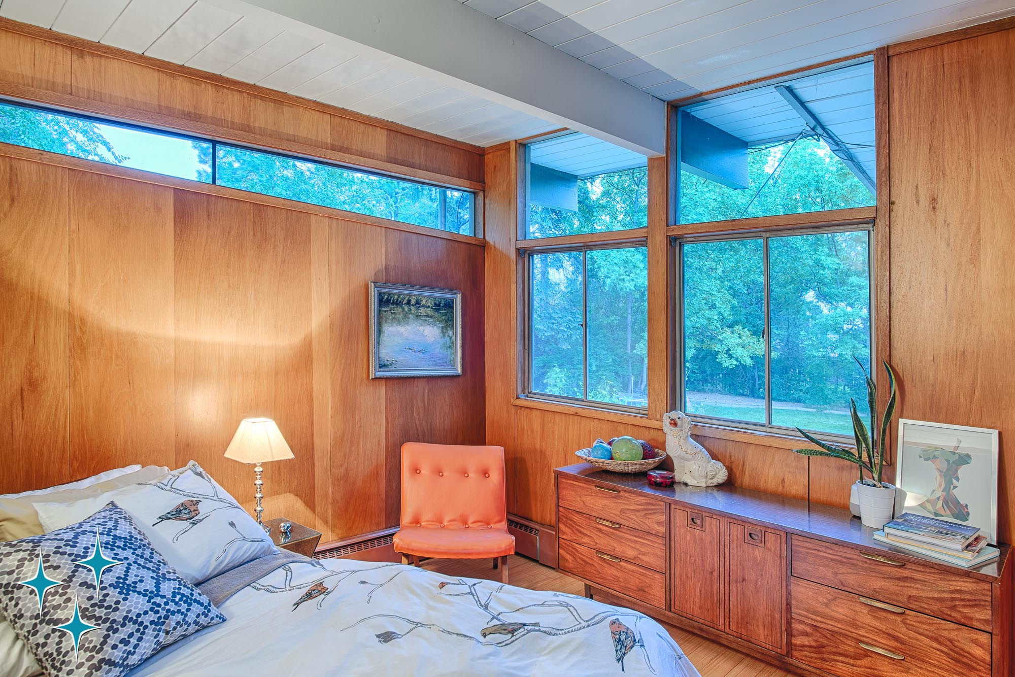 A wood-paneled bedroom at 4920 E Vassar Lane in Dahlia Acres, Denver featuring large windows with transoms and east-facing clerestory window. Designed by Frenchie Gratts and offered by Adrian Kinney, Broker Associate, Resident Realty South Metro