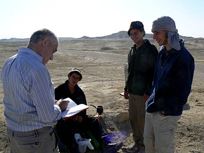 Jacob Saar signs a copy of his guidebook for a group of hikers in the Negev Desert.