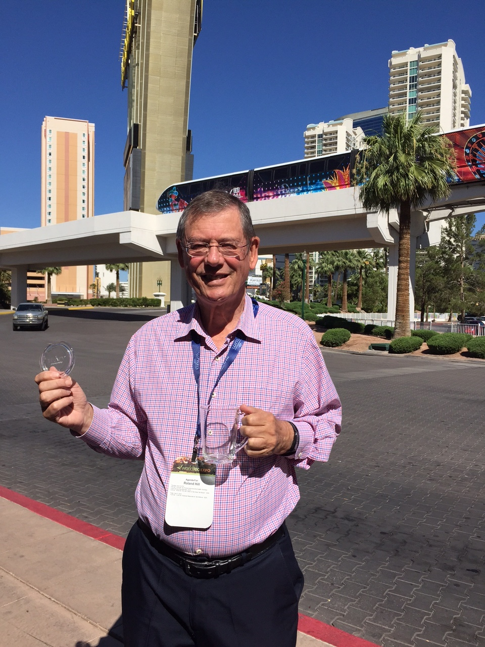 Roland Hill with TEAPY® at the World Tea Expo in Las Vegas. His Contra Vision one-way vision invention is shown on the windows of the monorail in the background.
