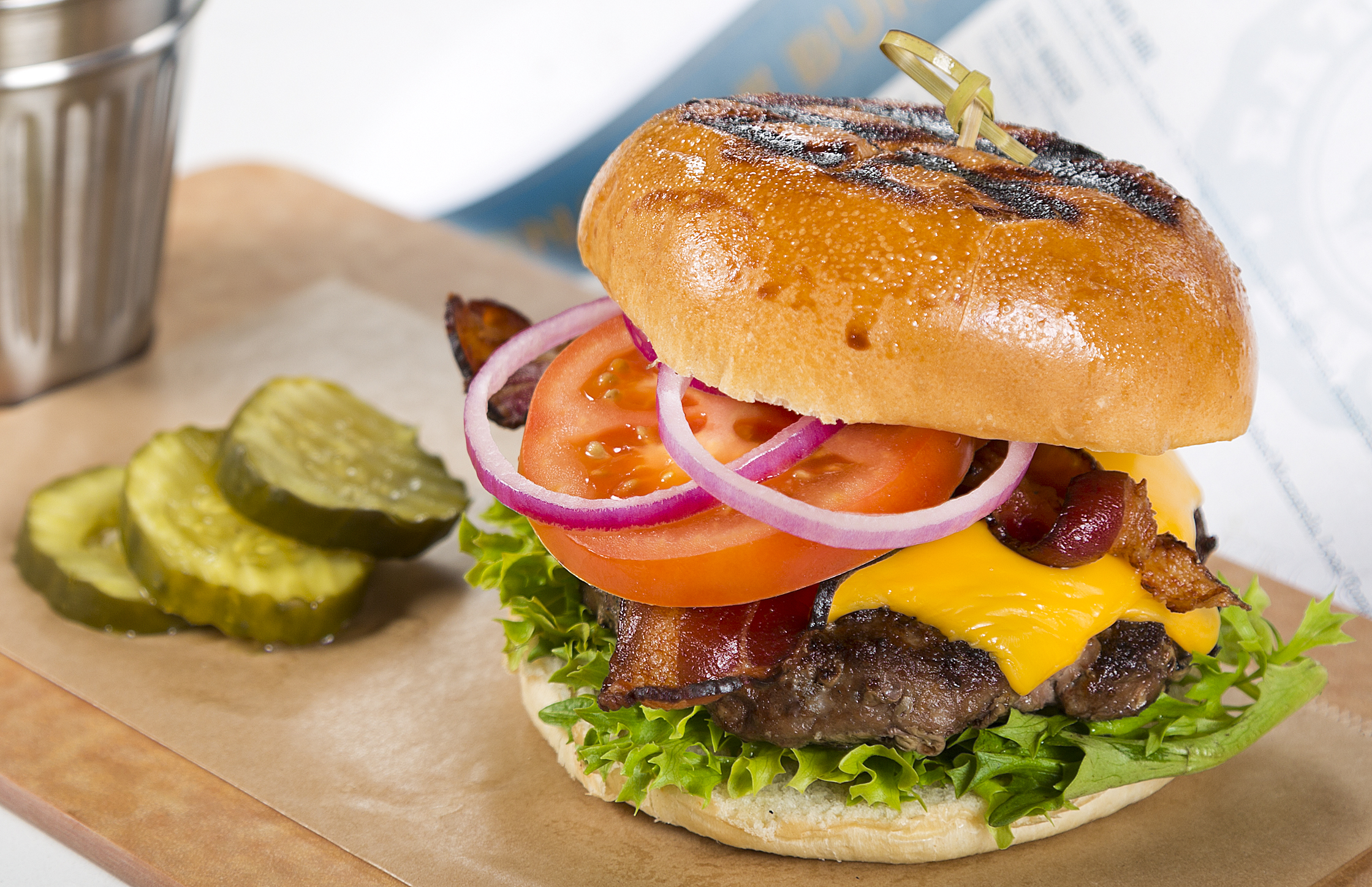 """BACKYARD BARBECUE   """"The All-American Classic"""" Signature Custom Blended Beef Grind, American Cheese, Garden Greens, Florida Tomato, Onion, Smoked Bacon, Barbecue Sauce, Toasted Brioche"""
