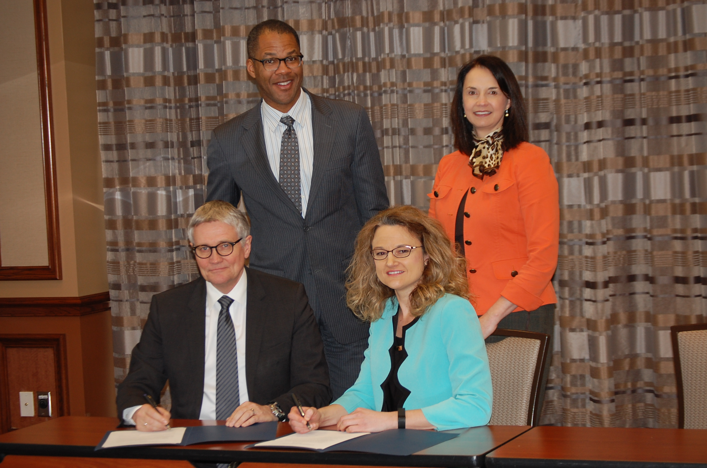 DOE Assistant Secretary of Fossil Energy Chris Brown and Chief Operating Officer Kim Greene (standing) join TCM Managing Director Roy Vardhiem and National Carbon Capture Center Director Roxann Laird (seated) in transferring the ITCN chairmanship and operation for the next two years.