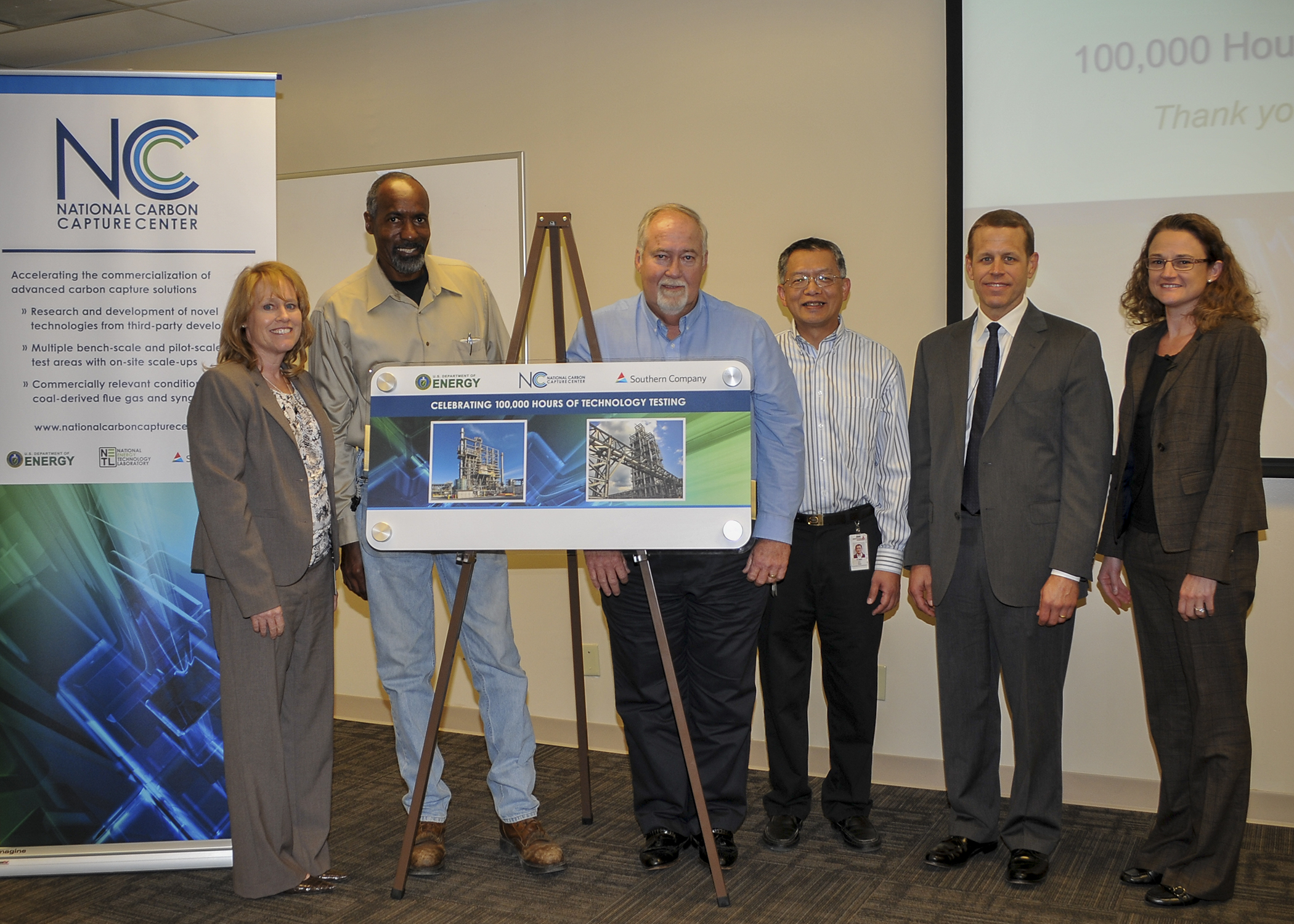 (L-R) Employees Michele Corser, James Woods, David Mims and Tony Wu accept a commemorative graphic from Alabama Power Senior Production Officer Jim Heilbron and Roxann Walsh, director of reduced-carbon, renewable and distributed energy R&D.