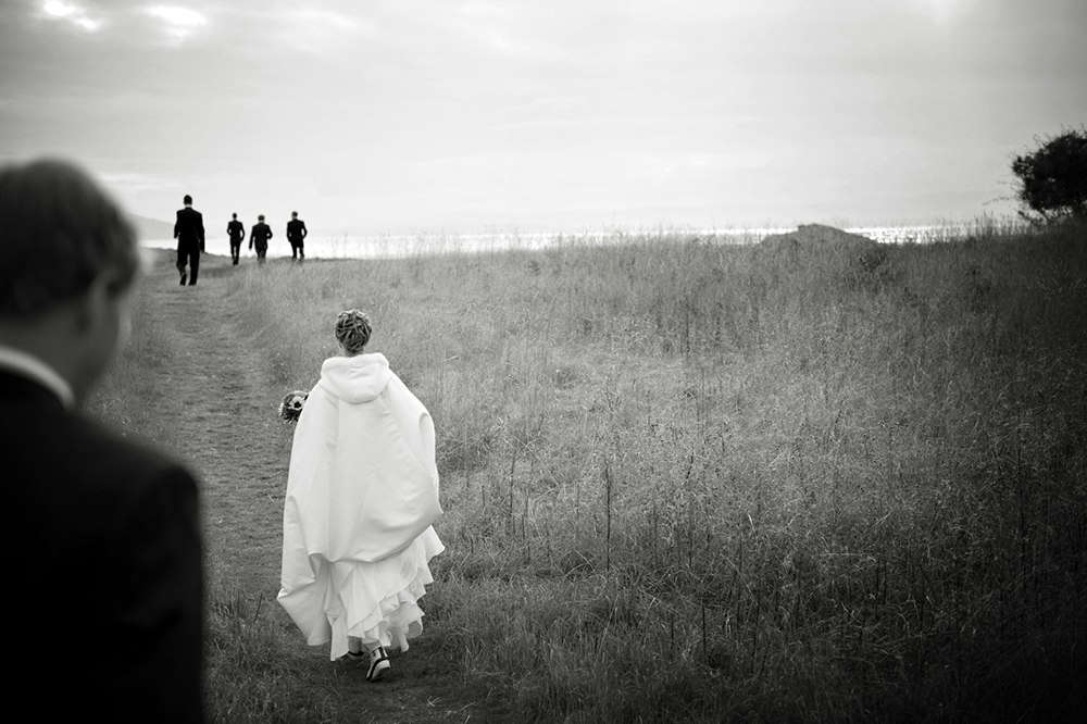 bride wearing a petti coat walking through a field, poet's cove bc