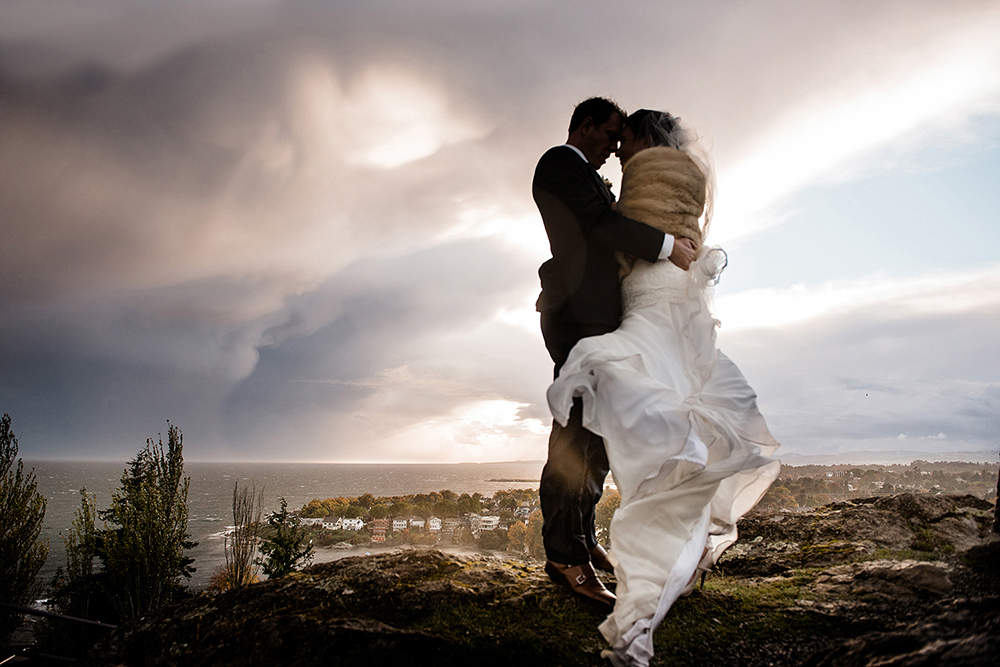 wedding couple embraces with an upcoming windstorm in Victoria BC