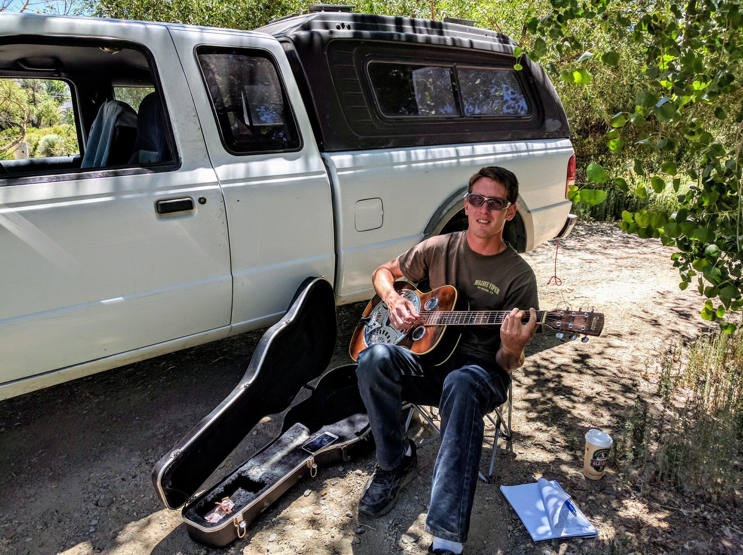 Teddy Ryan playing his guitar under the cool shade of a tree along the canal.