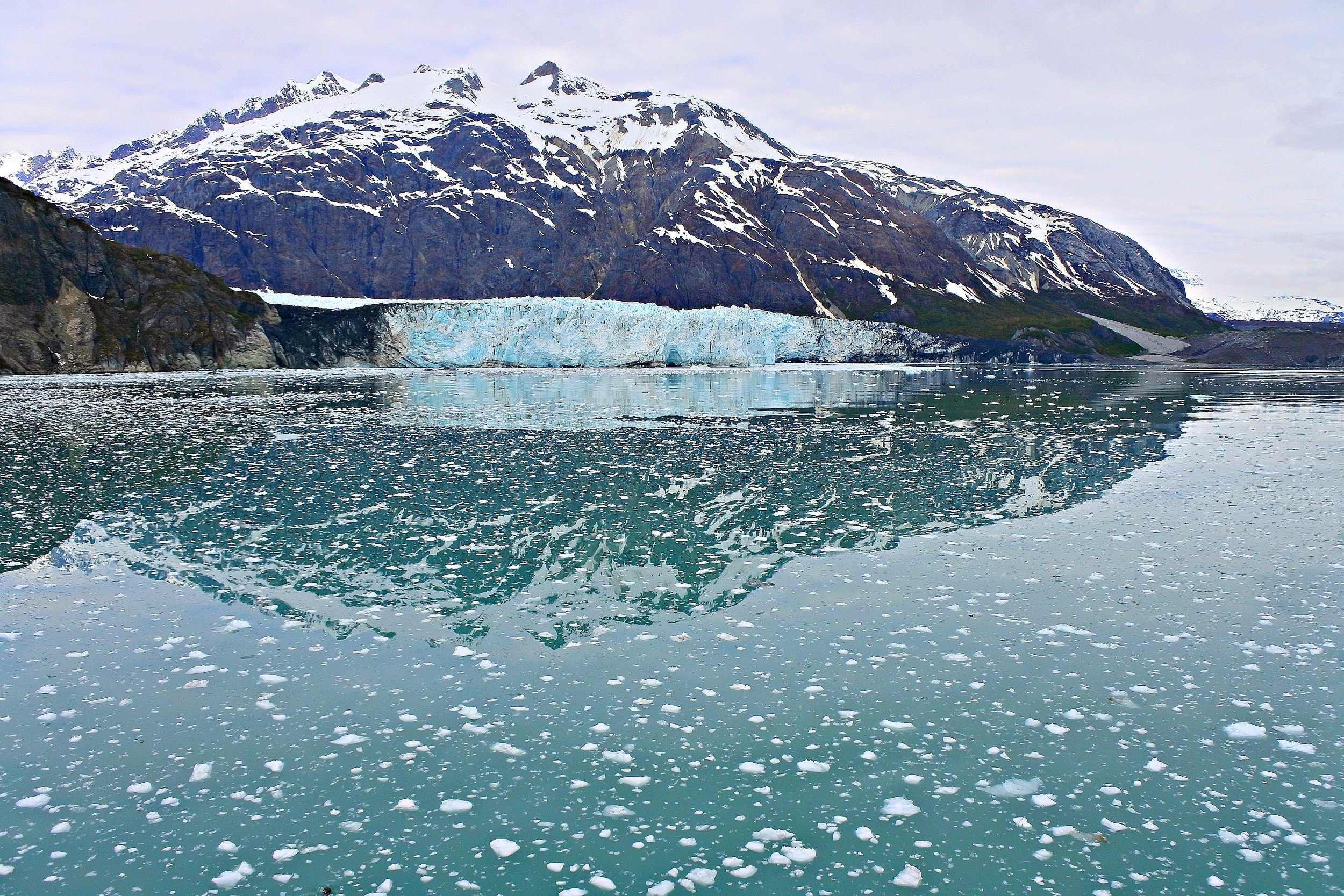 """Glacier Bay, Alaska. The block of blue ice beneath the mountain is a glacier. The white fluff on the water are pieces of ice that broke away from the bigger block during a process called """"caving"""""""