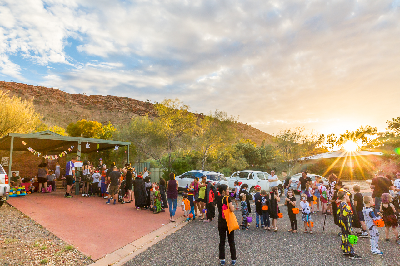 Patient zombies, witches, and vampires wait in line for candy as the sun sets over Alice Springs