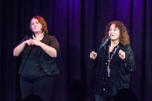 """Judith Stone (right) tells her story at Caveat in New York while Shelby Edwards interprets in sign language at our """"Communication"""" show. Photo by Nicholas Santasier."""