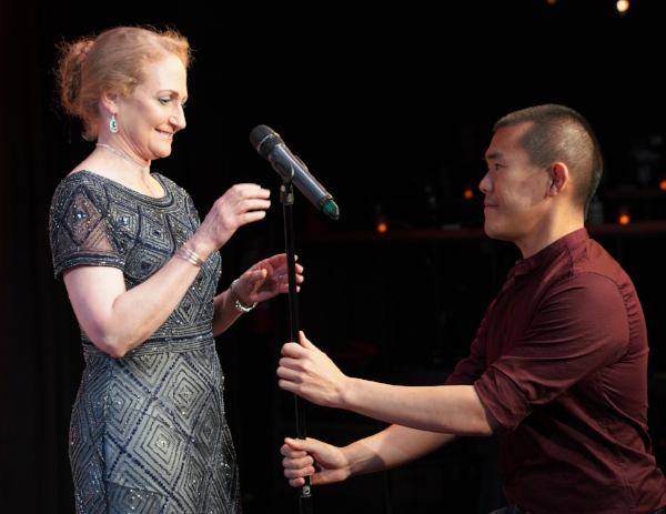 Host Ed Yong adjusts the mic for Jo Handelsman when she takes the stage at our first ever fundraiser in May 2018. Photo by Carly Hoogendyk.