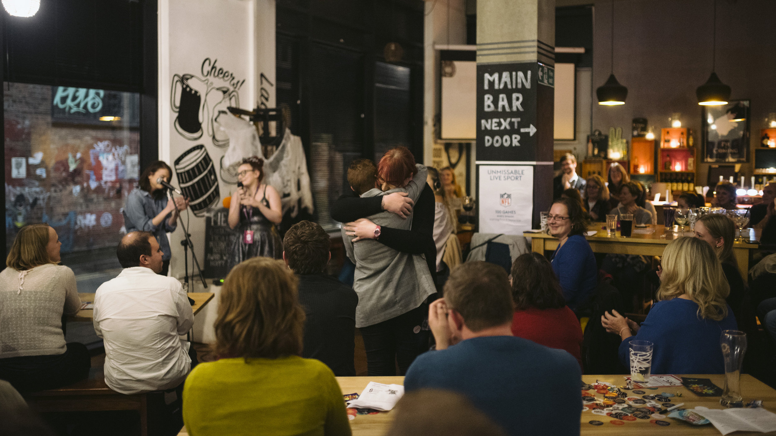 Charlotte Istance-Tamblin shares a hug with her wife at the Pie and Ale during the Manchester Science Festival in October, 2018. Photo by Drew Forsyth.