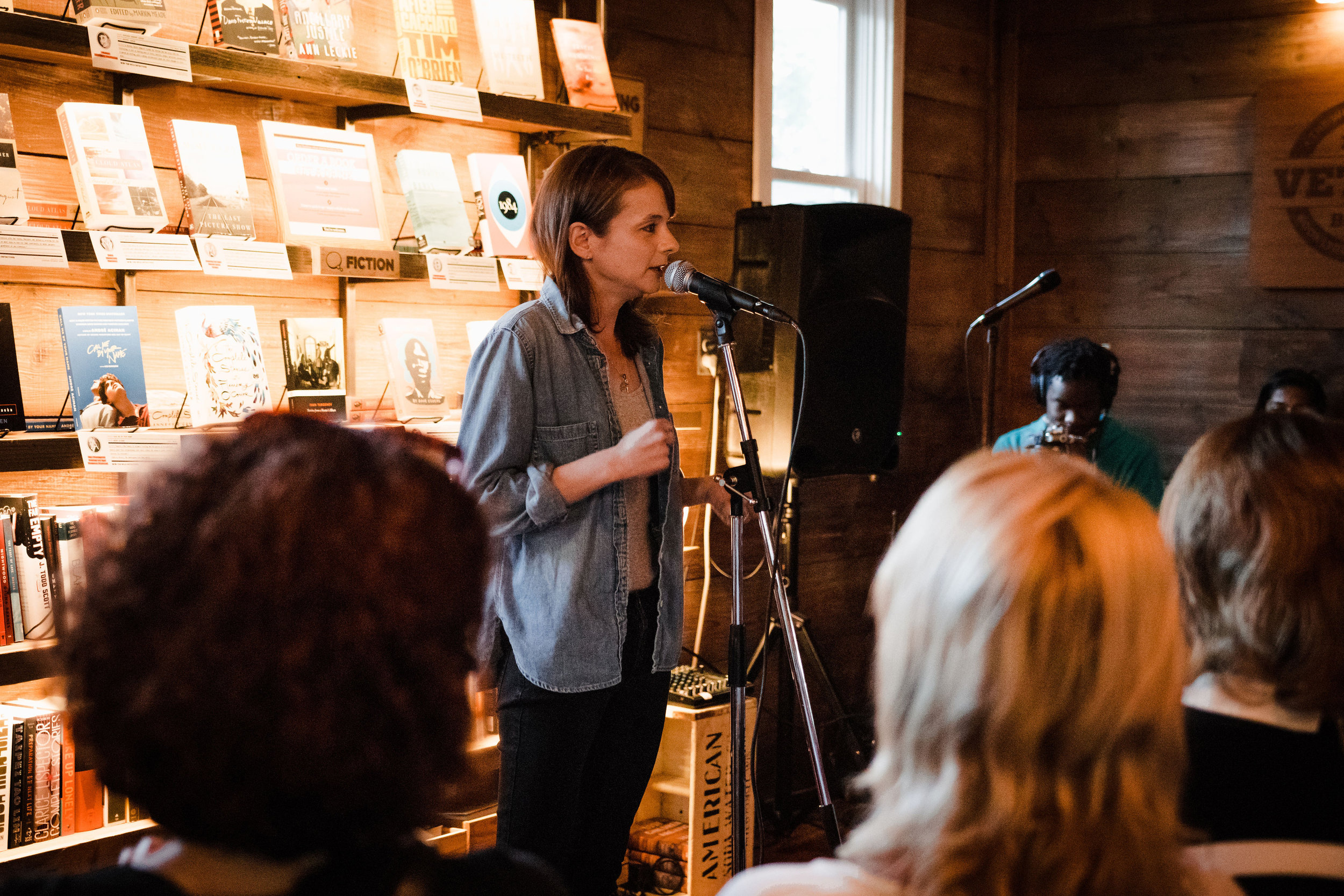 Artistic Director Erin Barker shares her story with our Story Collider audience at Wild Detectives in Dallas, TX in April 2019. Her mother is sitting in the front row (pictured right). Photo by Fallon Stovall.