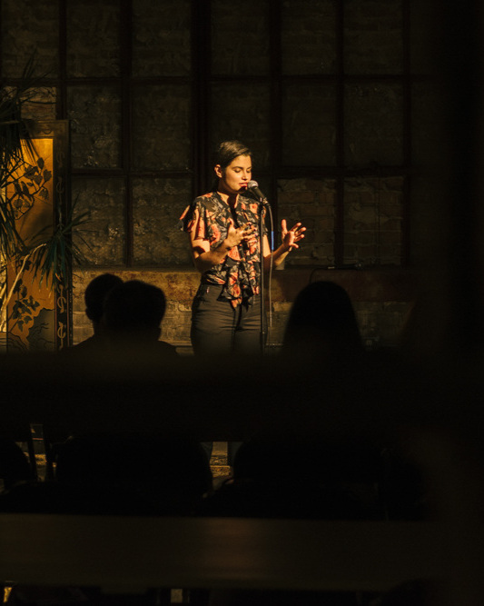 Anna Miller shares her story with the Story Collider audience at Dandy in Milwaukee, WI in June 2019. Photo by Mahdi Gransberry.