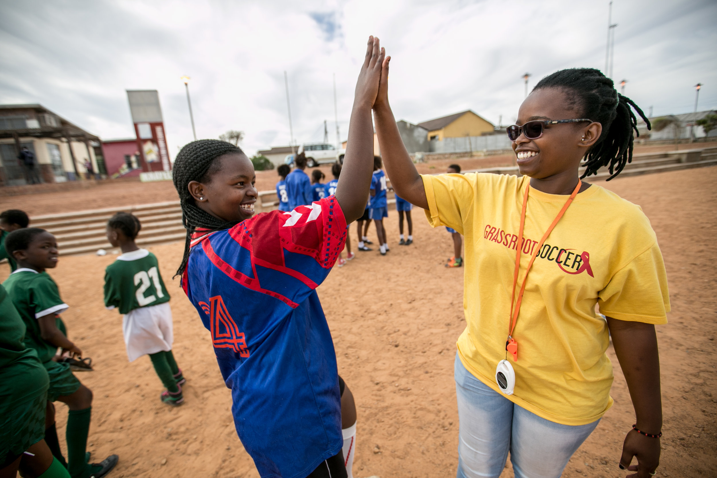 Photo: Courtesy of Karin Schrembrucker/GRS. SKILLZ. Coach Sonwabise (Sony) Dick celebrates with Grassroot Soccer SKILLZ Street graduate and volunteer, 15-year-old Yamkela Nqweniso, after a successful afternoon of SKILLZ HIV-awareness activities with female SKILLZ participants in Khayelitsha, South Africa's fastest growing township.
