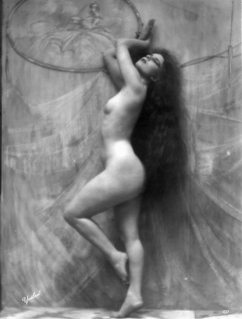 A nude woman with long dark hair strikes a graceful pose, circa 1900.